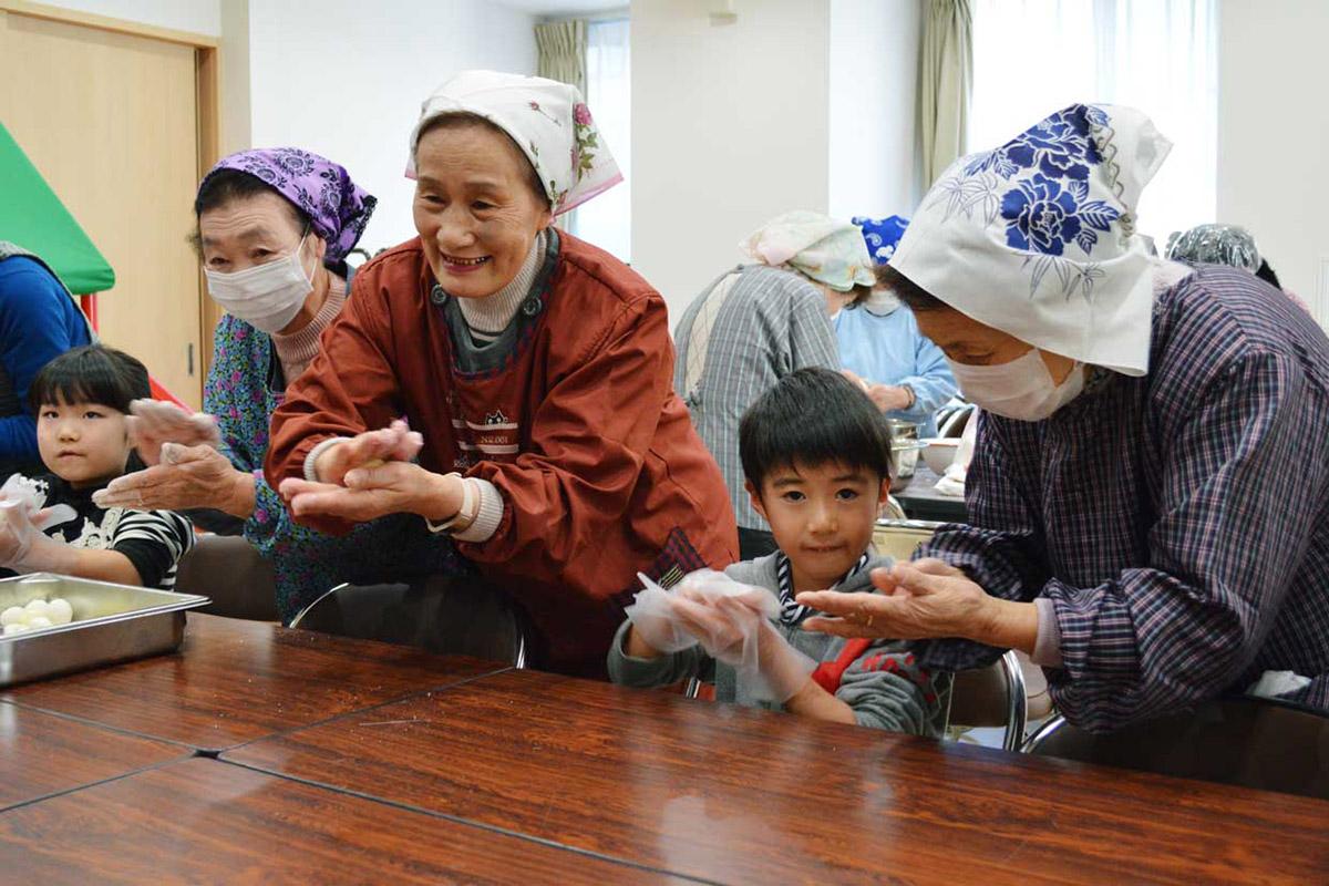 一緒に小正月の団子作りを楽しむ子どもと復興住宅の住民
