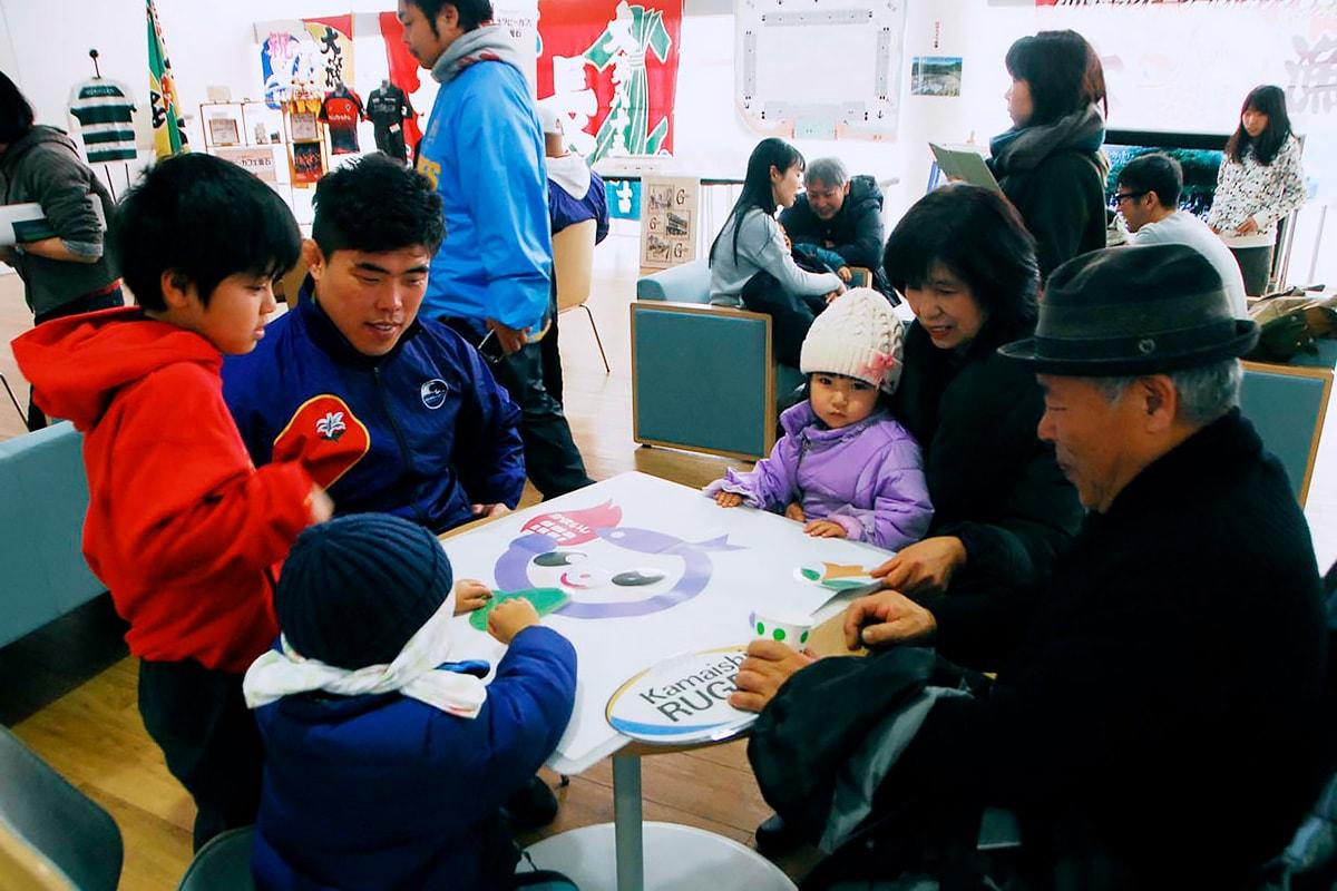 ラグビーにちなんだ福笑いゲームを楽しむ家族連れと釜石SWの許選手
