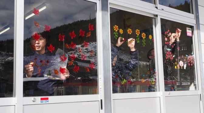 昇降口に最後の飾り付けを行う唐丹小OBら。テーマは「春夏秋冬」