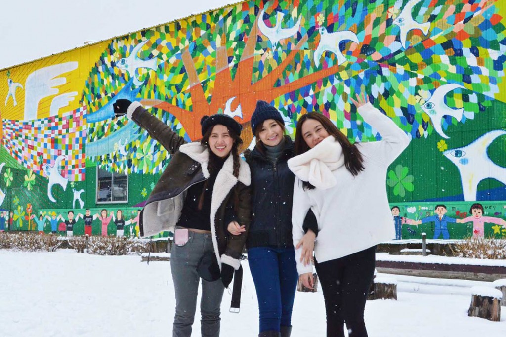 タイの若い女性らは「雪の釜石」を楽しみ、SNSで発信した=10日、こすもす公園で