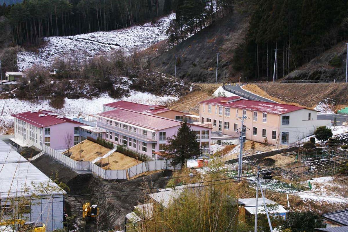 高低差25メートルの敷地に建物を分棟、市松状に配置された唐丹小中の新校舎