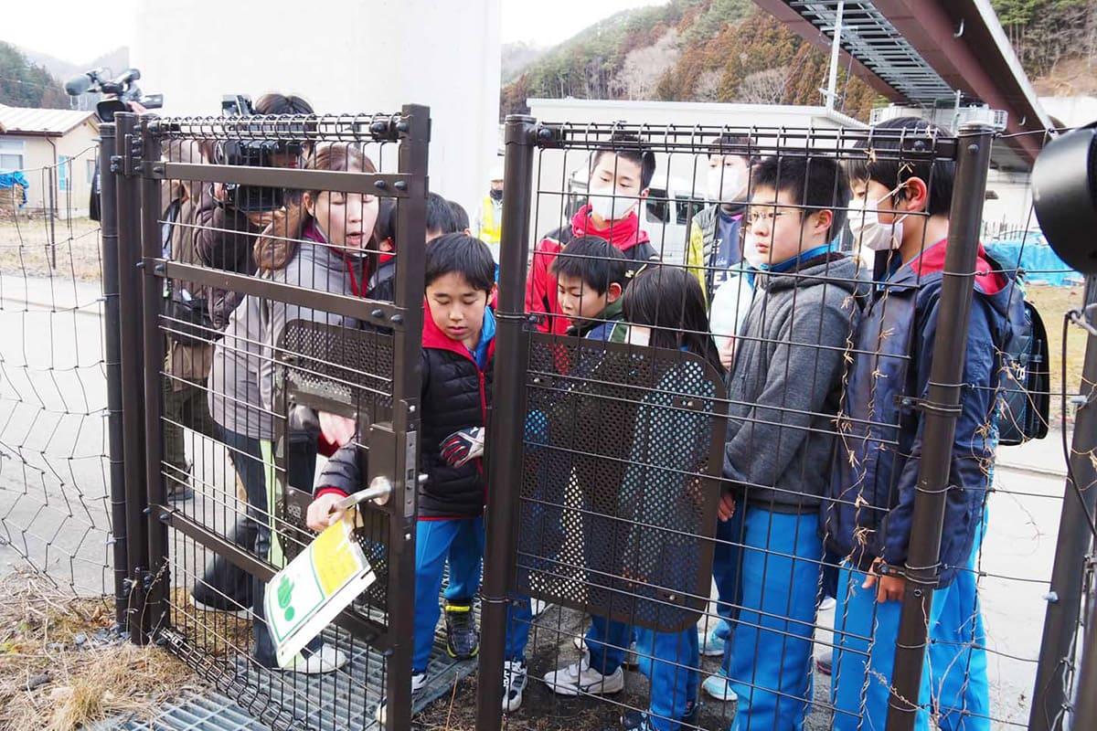 扉に付いたアクリル板を外し、避難階段に進入する児童ら