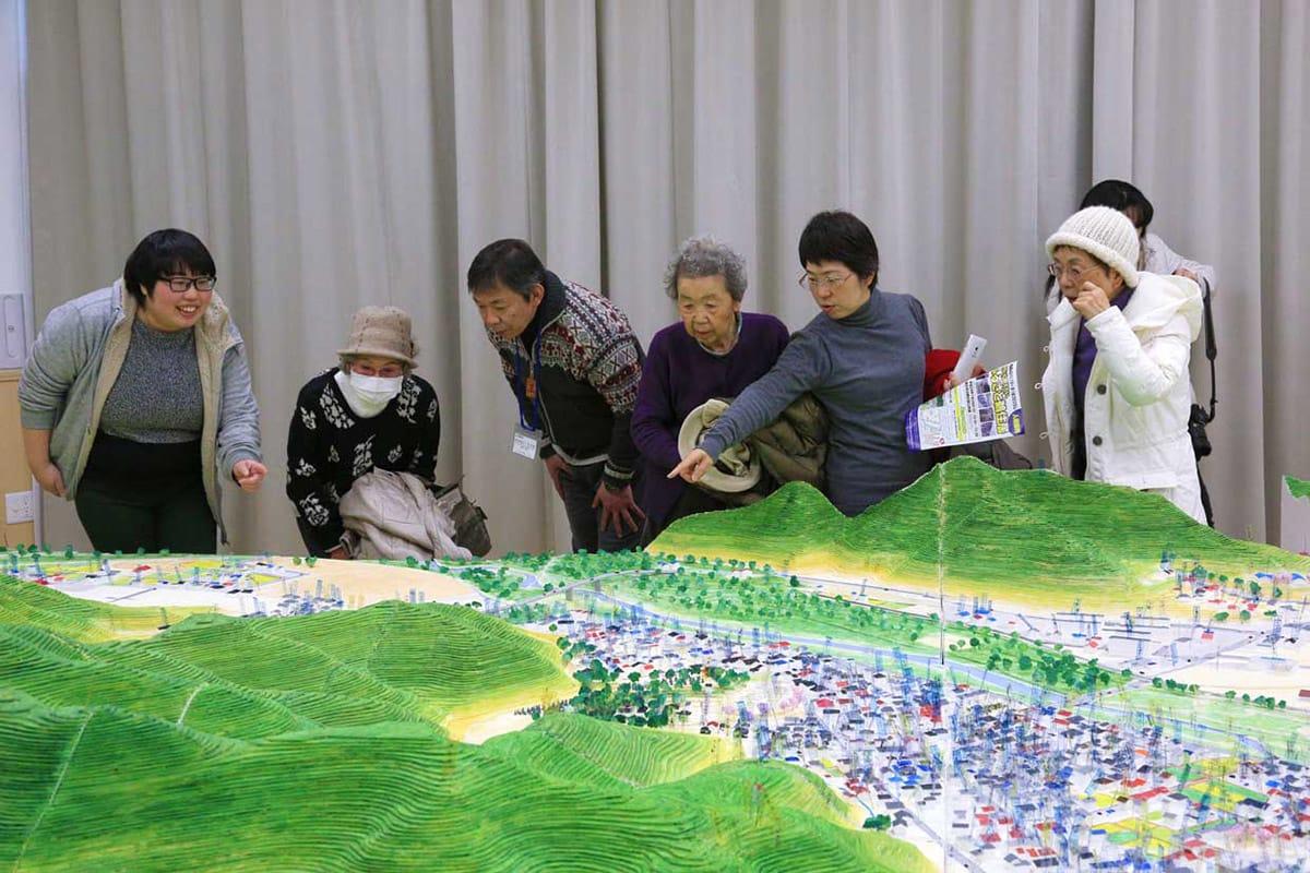 模型を見ながら震災前のまちに思いをはせる人たち