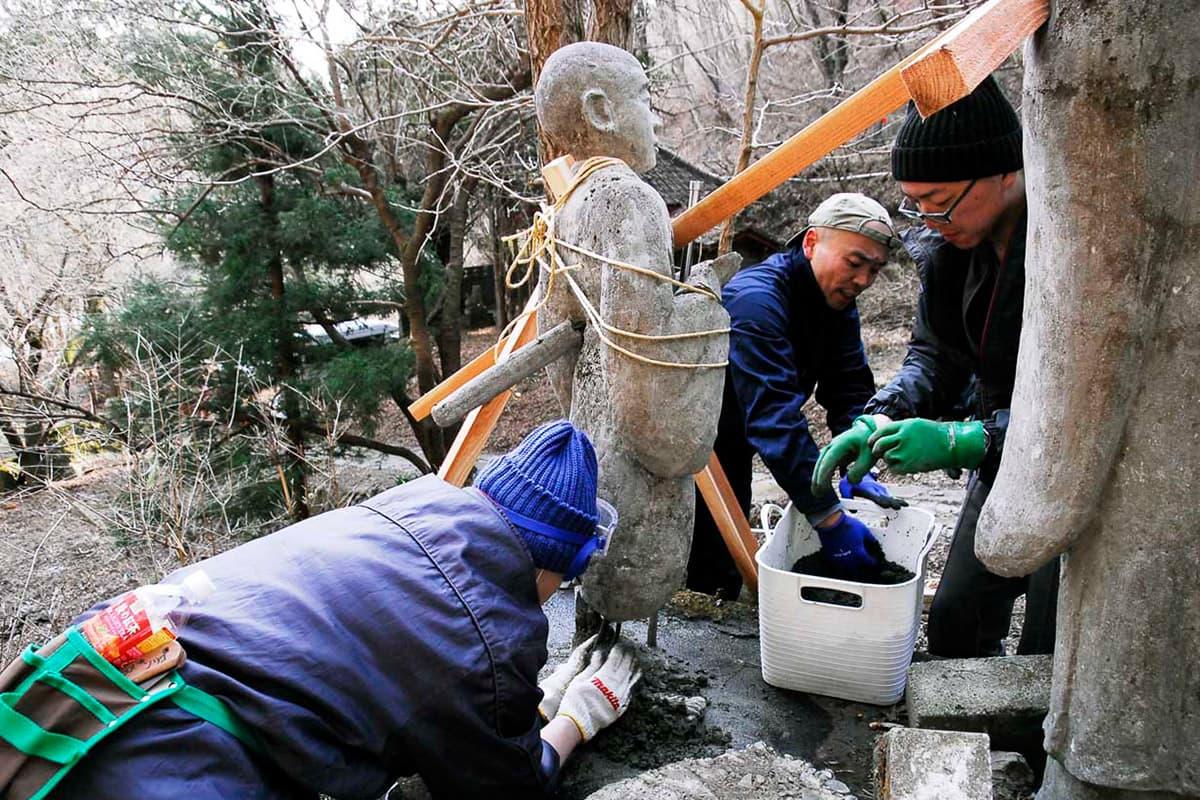 釜石霊場入り口の石像を修繕する北海道霊場会の僧侶ら