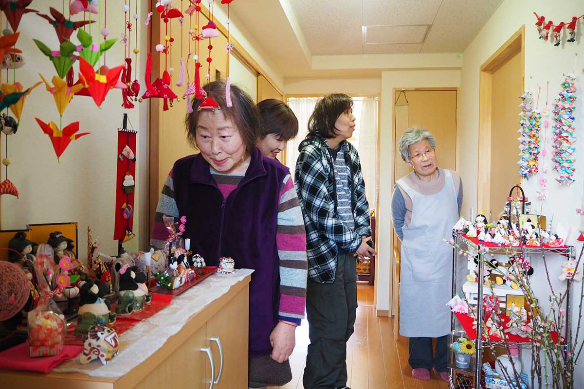 平田復興住宅の玄関を彩るひな飾り。震災後、二川さん(右)が集めた約30点が、心温まる世界をつくり出す