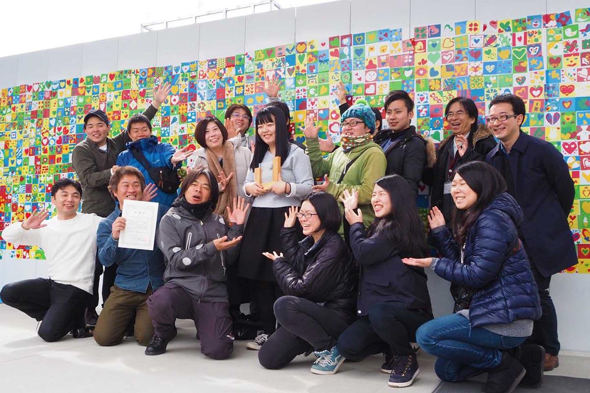 日比野克彦さん(前列左から3人目)や応援者らに囲まれ、笑顔を見せる寺崎幸季さん(中央)