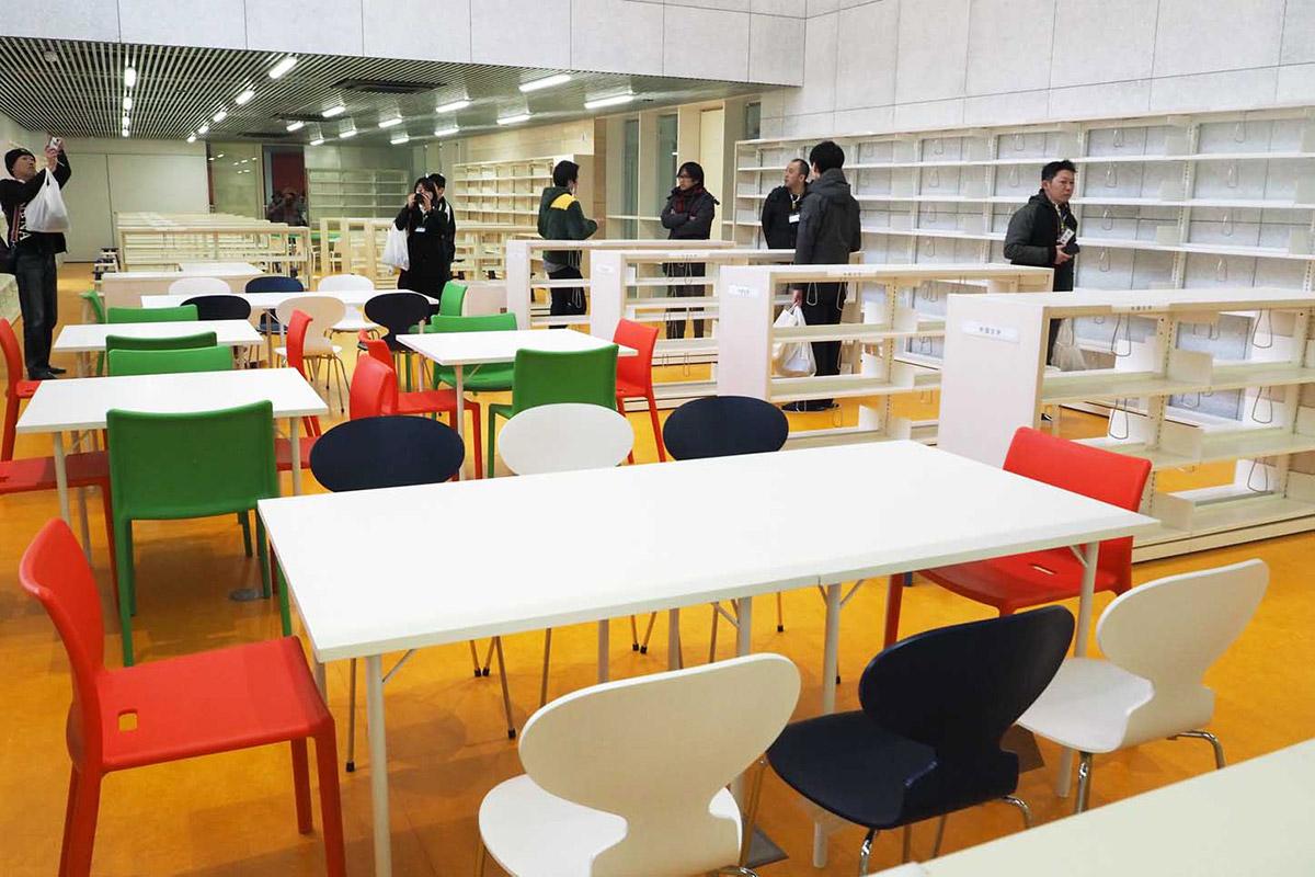 白を基調とした空間にたくさんの本棚、カラフルないすが並んだ図書室