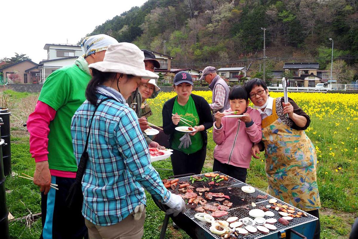 花畑で交流を楽しむ地域住民とボランティア