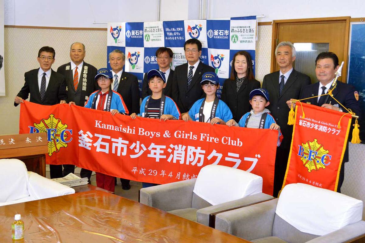 坂本さん(左端)が寄贈した装いで横断幕を掲げる「釜石B・F・C」の児童と関係者