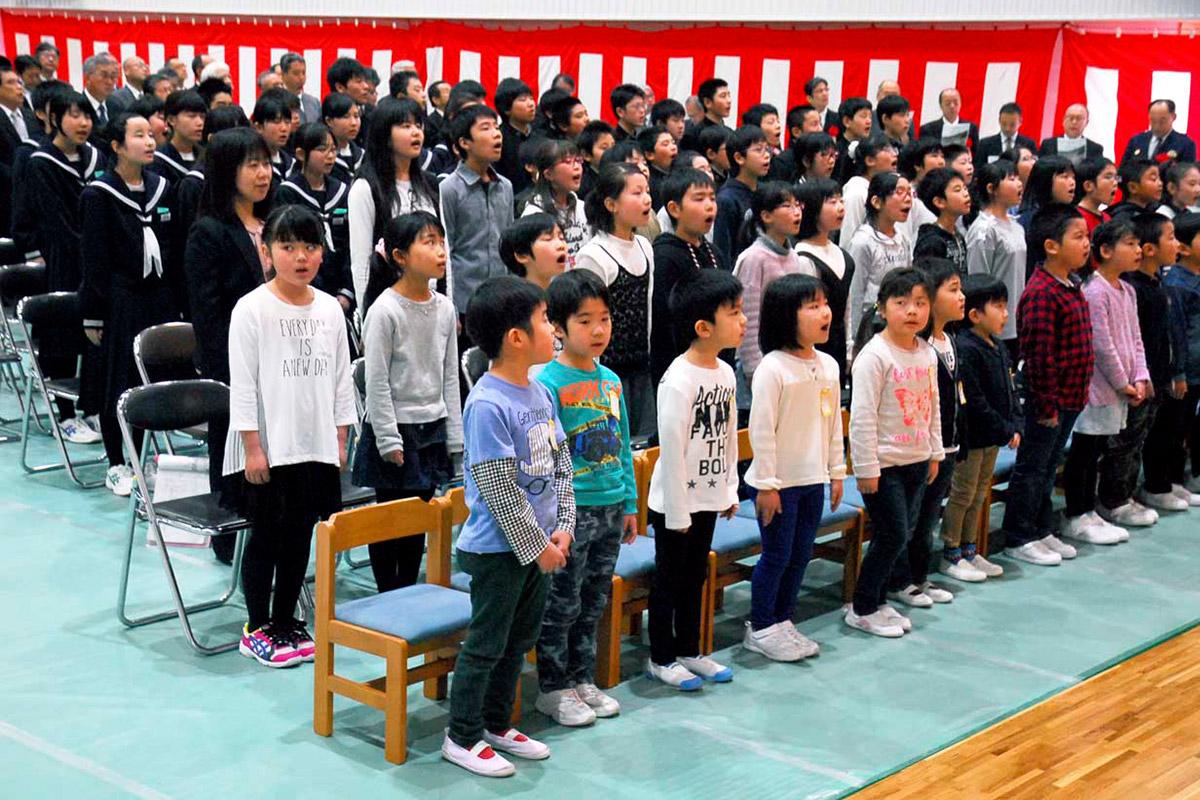「校歌を斉唱し地域住民らと新校舎完成を祝う唐丹小、中生