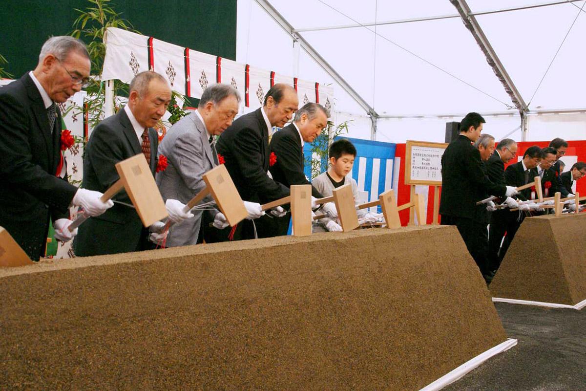 復興スタジアムの無事完成を願い、くわ入れする野田武則市長ら関係者