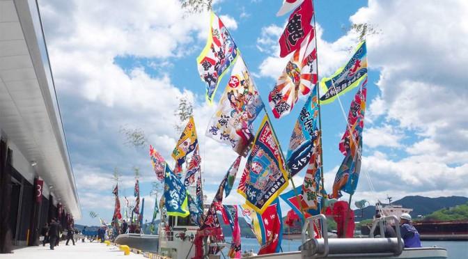 式典には漁師らも祝いの大漁旗を掲げて新しい魚市場に駆け付けた