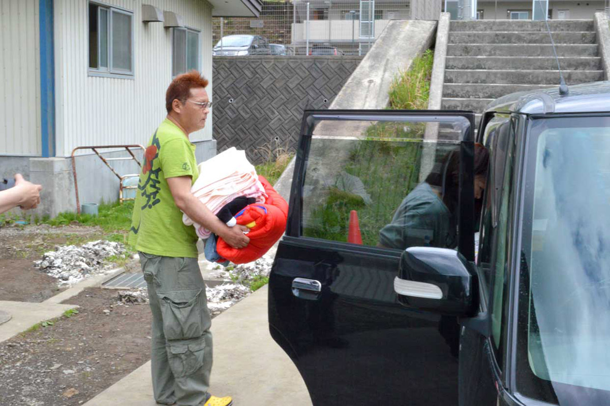 手荷物を自家用車に積み込み、帰宅準備する避難者=11日午後2時46分、旧釜石商高