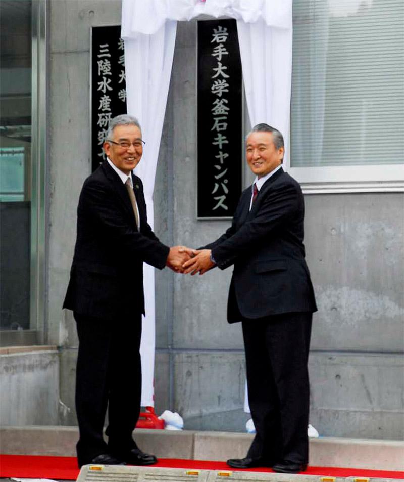 看板を除幕し、今後の連携へ固い握手を交わす岩渕学長(左)と野田市長