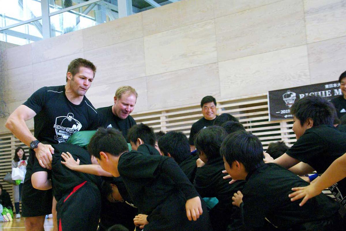 子どもらの力強いスクラムに笑顔で応戦するマコウさん(左)、マコーミックさん