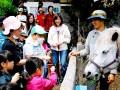 三陸駒舎の黍原豊さん(右)に教わりながら馬との触れ合いを楽しむ親子ら