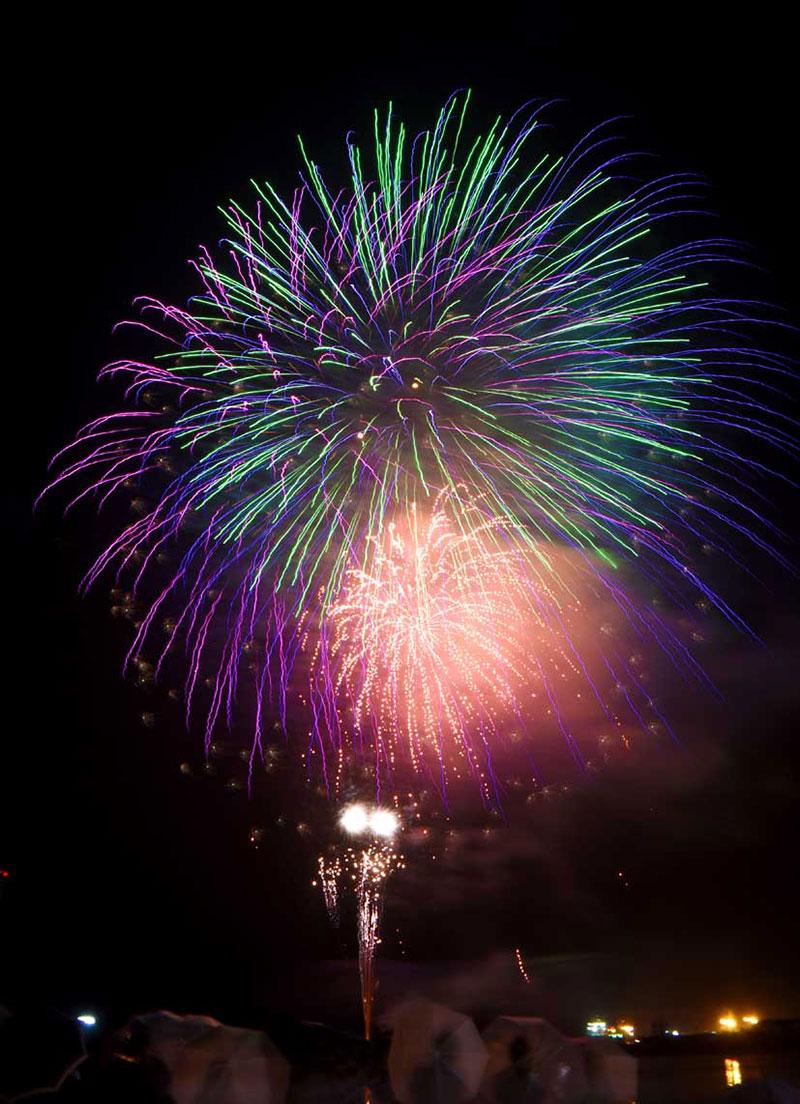 釜石港内を彩る納涼花火。雨模様を突き、2年ぶりに開かれた=12日夜