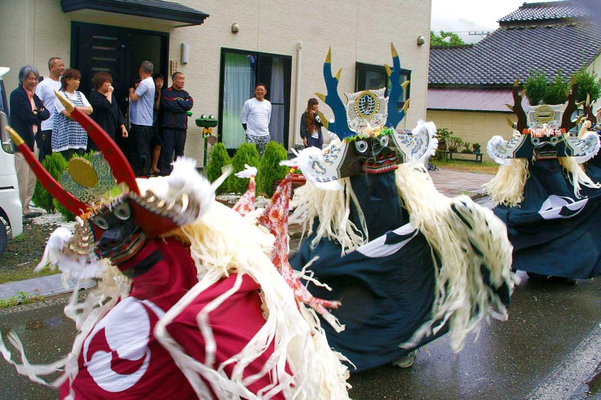 震災後移住した住民宅前で踊りを披露する砂子畑鹿踊