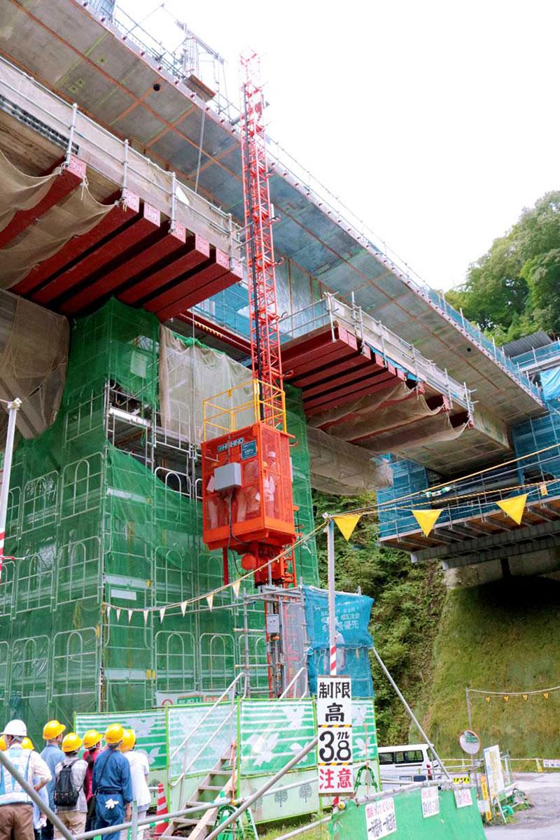 高さが20メートル以上もある八雲跨道橋を橋脚の下から見上げる参加者ら