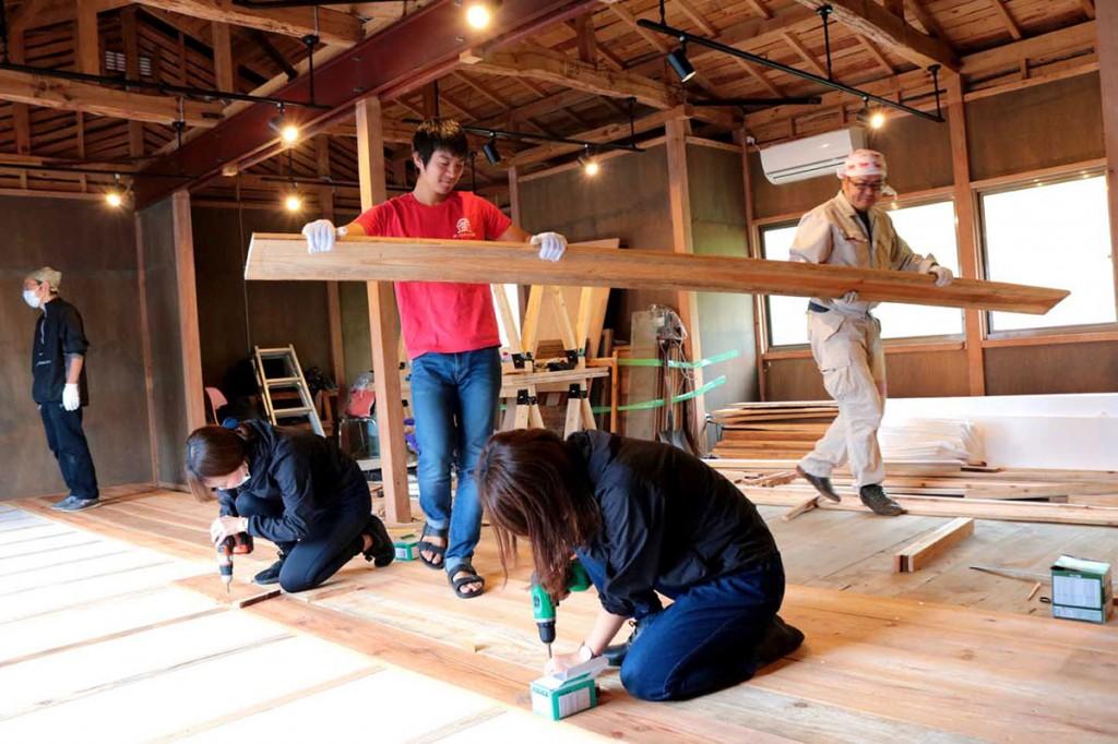 被災木を製材した板を床に貼る作業に取り組む関係者