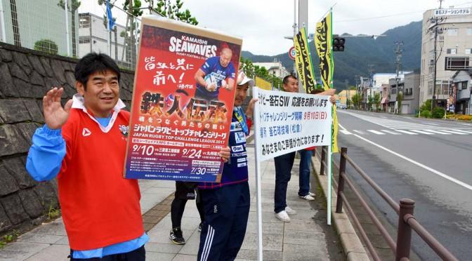釜石駅前に立ち、TCリーグ開幕をPRする「V7戦士」の坂下功正さん(左)ら新日鉄釜石ラグビー部OB