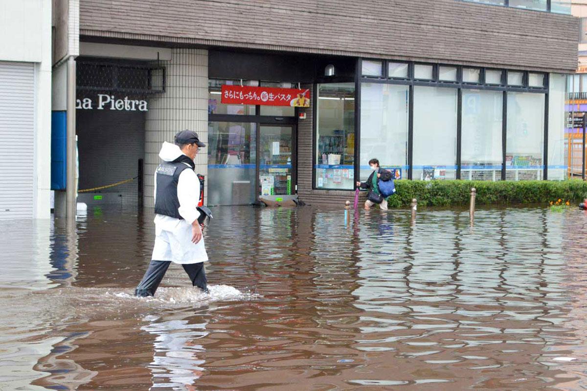 18日朝、出勤する女性は膝まで濁水につかり、目抜き通りを渡った