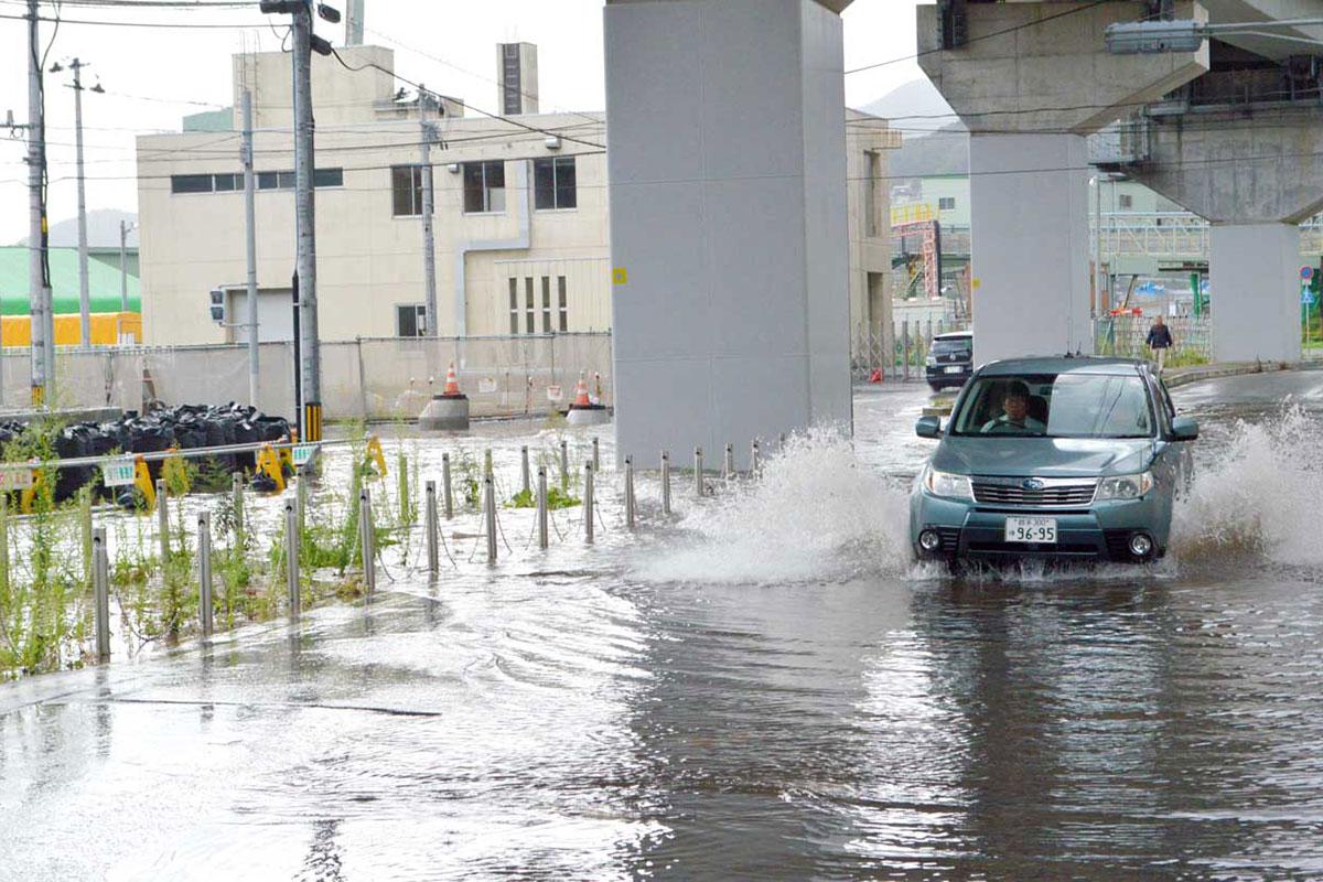冠水した市道を水しぶきを上げて進む車=18日朝、只越町(