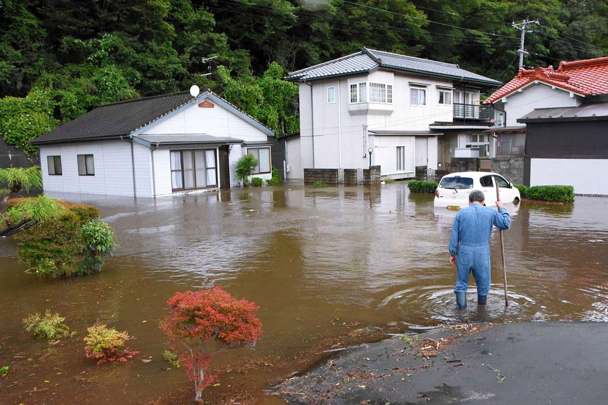 大雨で水につかった住宅や車=18日朝、住吉町
