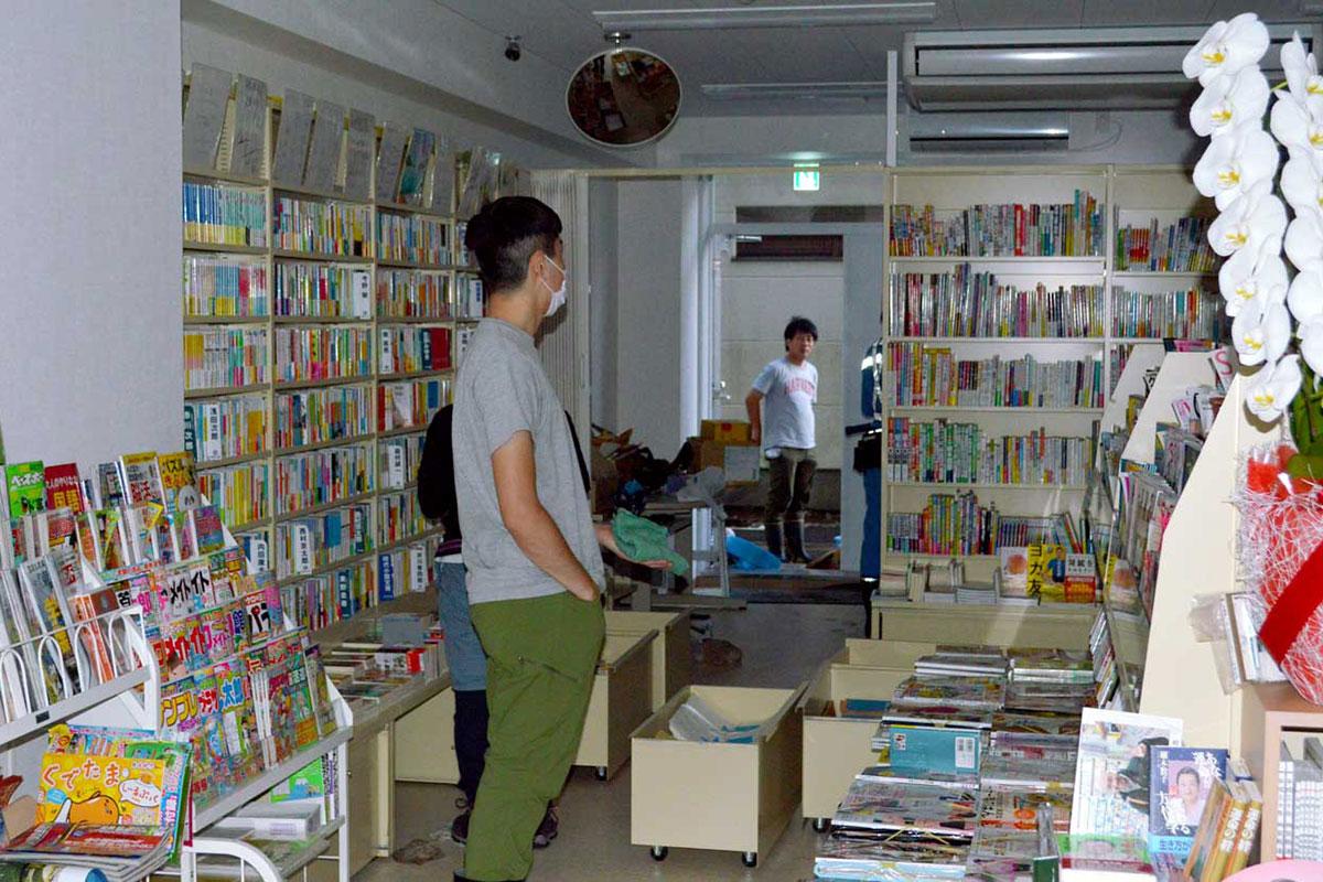 床上浸水の書店は排水と乾燥に懸命の作業=18日夕、大町