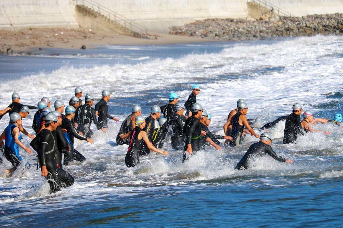 海岸に打ち寄せる波を越えスイムに挑む選手ら=午前8時