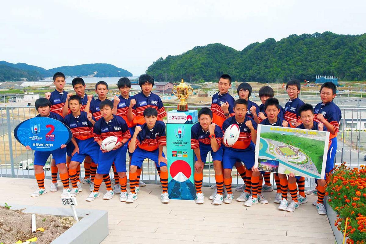 建設中のラグビーW杯会場の前で優勝トロフィーとともにポーズをとる釜石東中特設ラグビー部員
