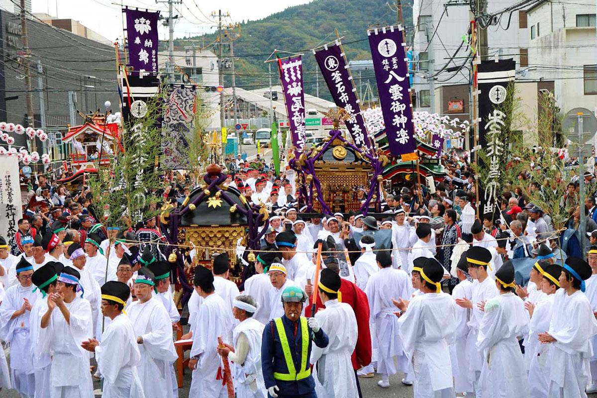 震災から復興しつつある新しいまち並みの中を進む尾崎神社と新日鉄住金釜石山神社のみこし=15日
