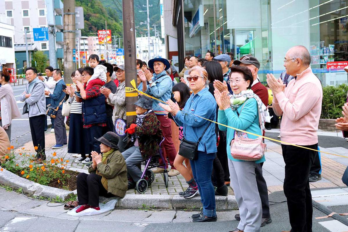 見物客は通りで披露される芸能に盛んな拍手を送った=15日