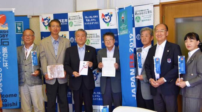 のぼり旗を掲げ、ラグビー基金を寄付した石村眞一代表(中央)ら