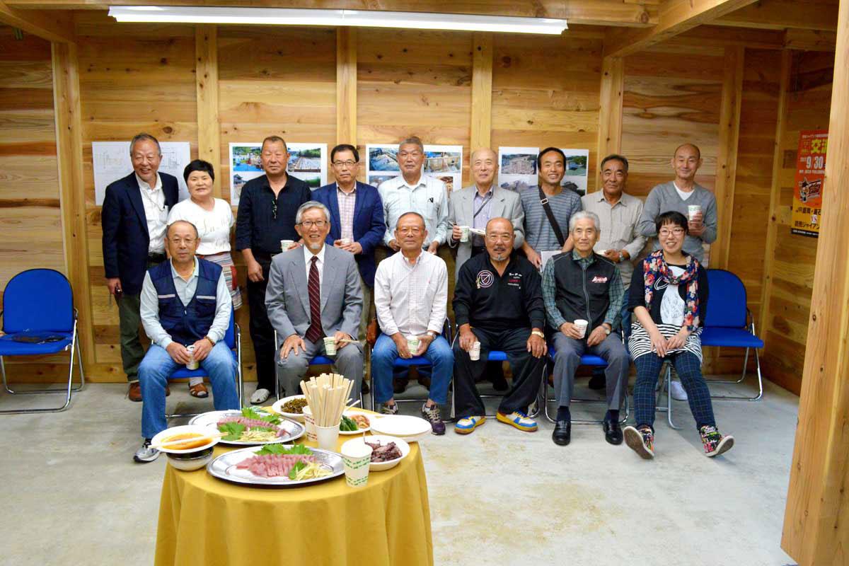 お披露目の会で仲間と剱持さん(後列中央)は「新居」の完成に笑顔いっぱい