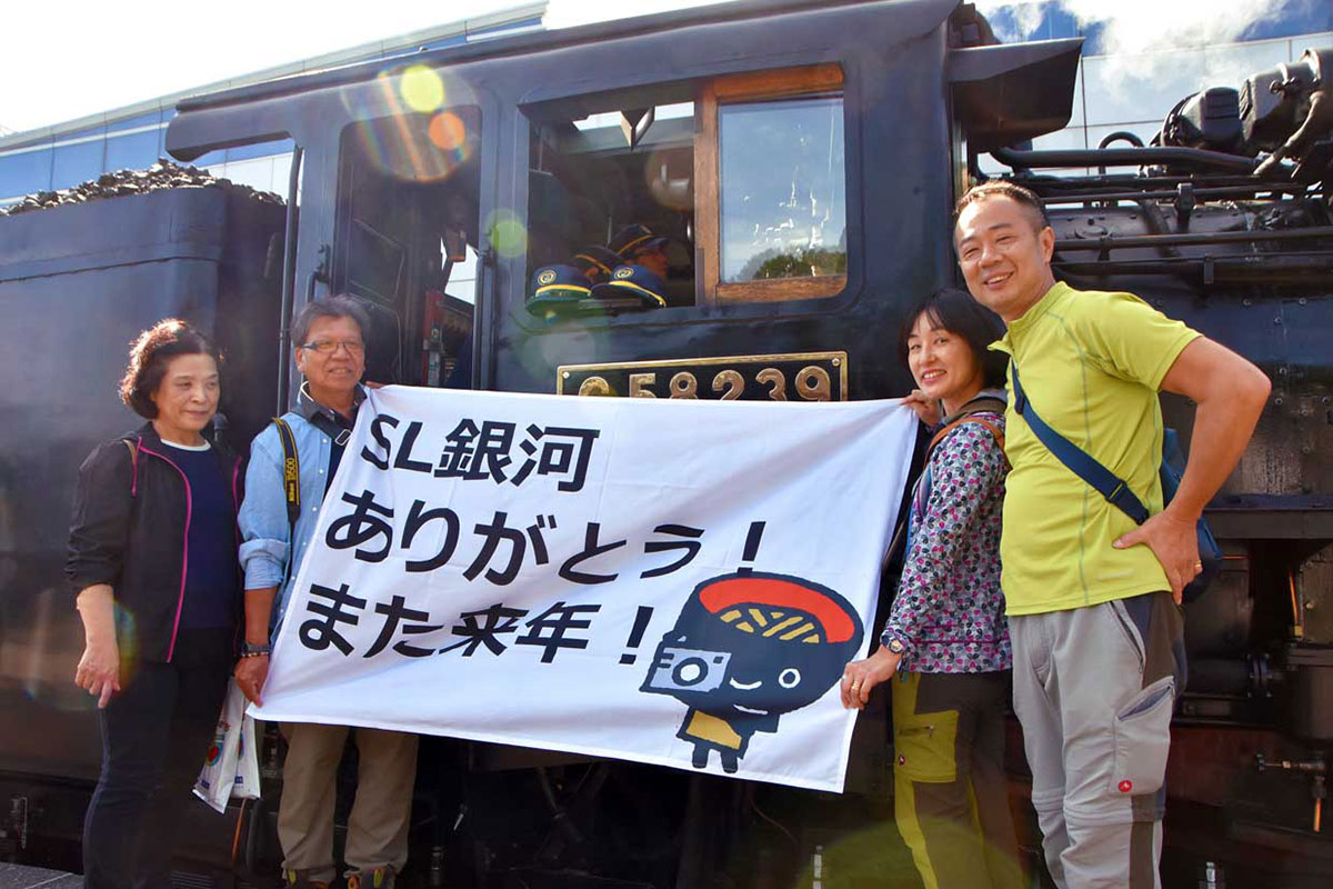 「ありがとう! また来年!」の横断幕を掲げて乗車する辻本一夫さん(右)