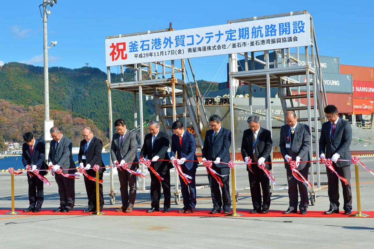 外国貿易コンテナ定期航路開設を祝い、期待を込めてテープカットする関係者