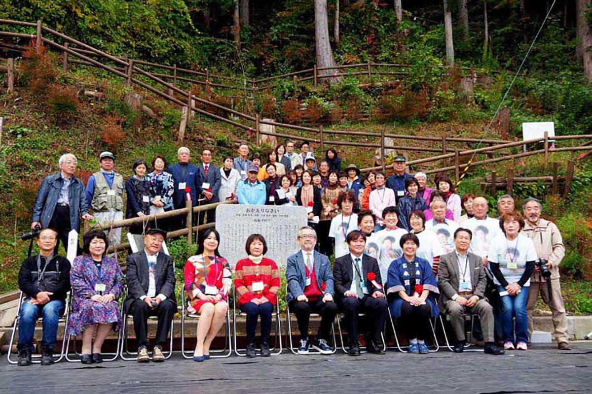 音声装置が加わった島倉千代子さんの歌碑の前で関係者らが記念撮影