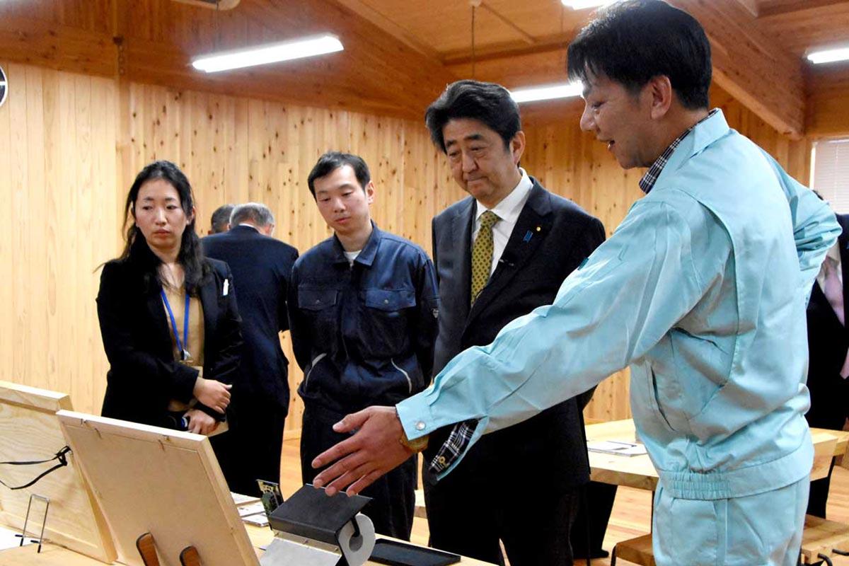 鉄と木のコラボ製品について髙橋幸男参事(右)から説明を受ける安倍首相