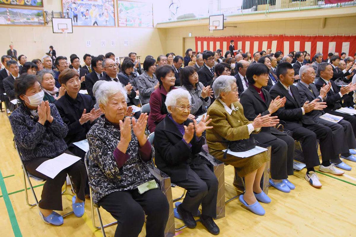 児童の歌声に拍手を送る落合ハルさん(前列左)