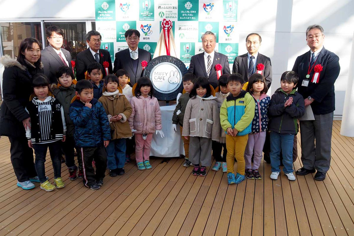 かわいらしい「ミッフィー」をデザインしたマンホールのふたを笑顔で囲む釜石小1年生
