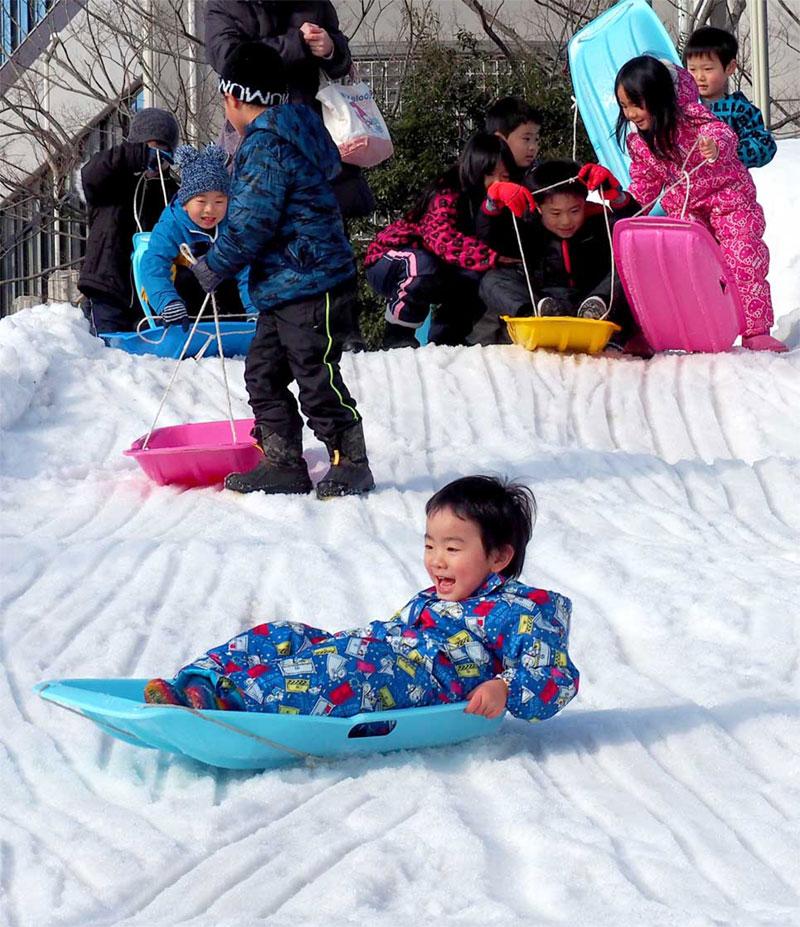 横手市の雪で作った滑り台は今年も大人気。そり遊びに夢中になる子どもたちの笑顔が広がった