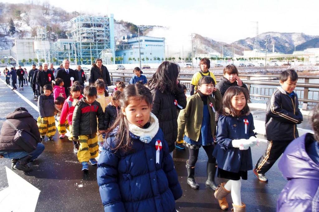中心市街地のにぎわいや釜石港の物流機能強化につながると期待される千年橋を渡り初めする子どもたち