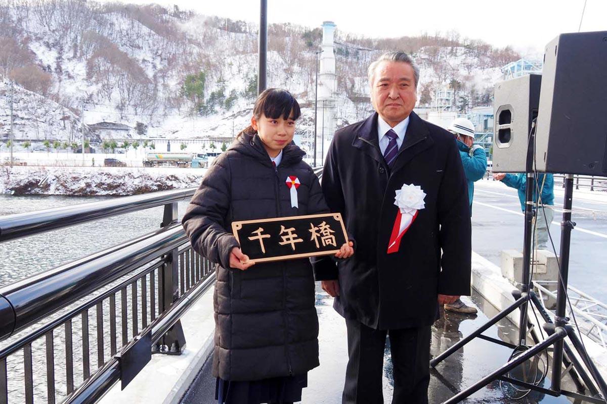 揮ごうした橋名板を持つ命名者の大瀧結菜さん(左)、野田武則市長