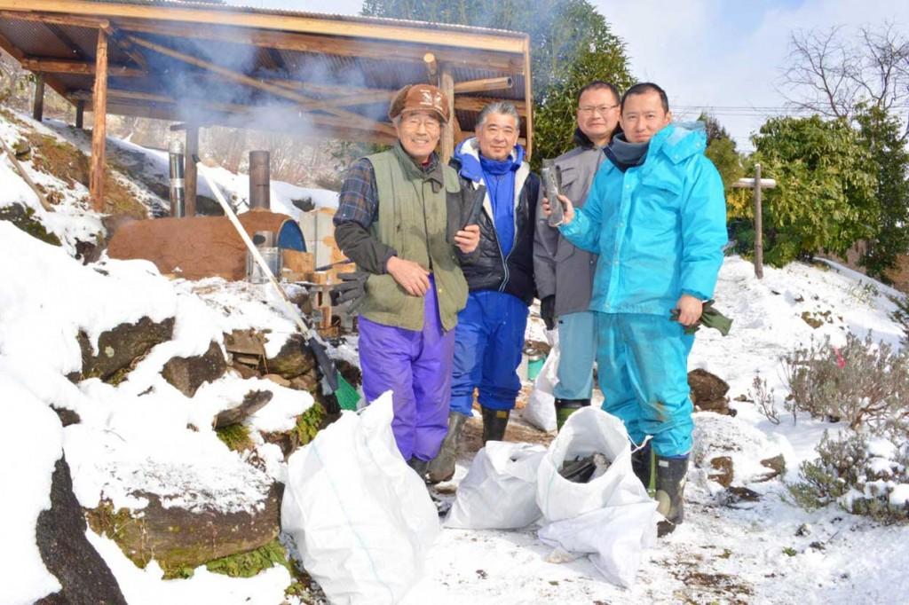 雪景色の中で技術を高める「炭焼き人」(左端・小澤さん、右端・山口さん)