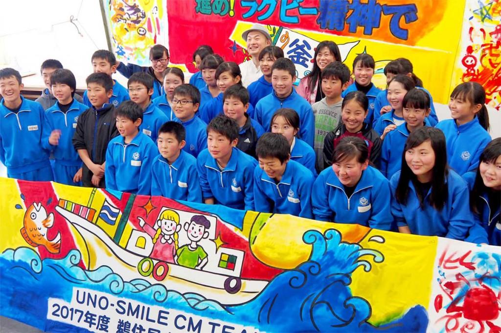 卒業制作も兼ねたCM撮影で使う大漁旗を完成させ、笑顔を見せる鵜住居小の6年生