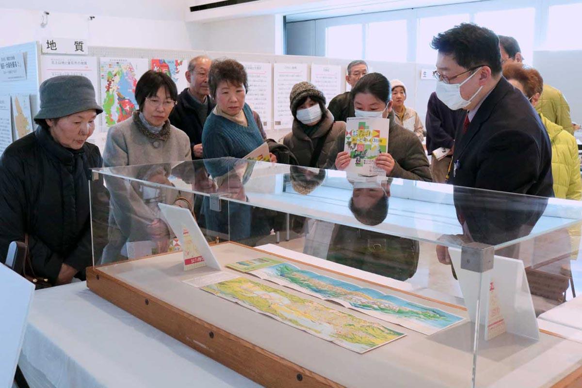 釜石の鳥瞰図の説明を聞く来場者。1枚は市制施行記念で発行