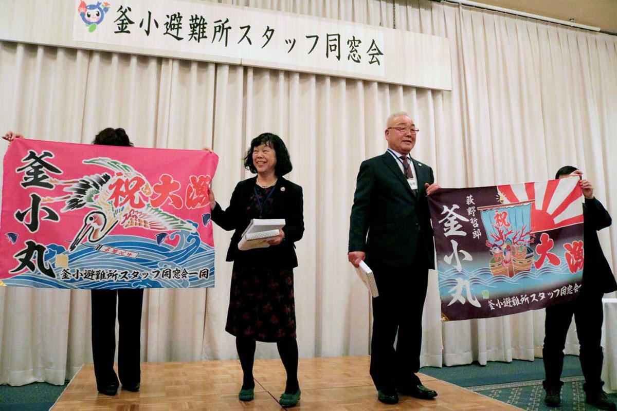 サプライズで贈られた大漁旗を広げる加藤さんと荻野会長
