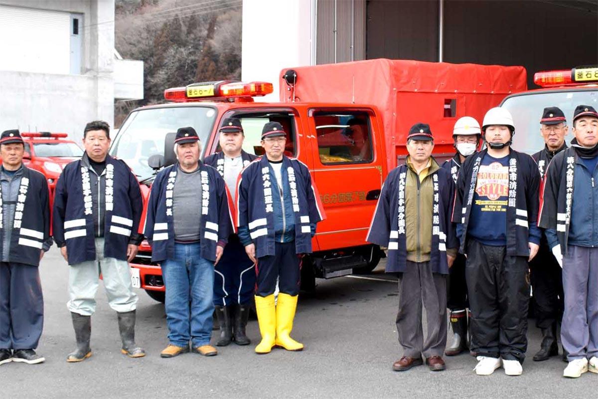 新しいポンプ、積載車の配備を喜ぶ消防団第6分団第7部(左)、第8分団第6部の団員ら