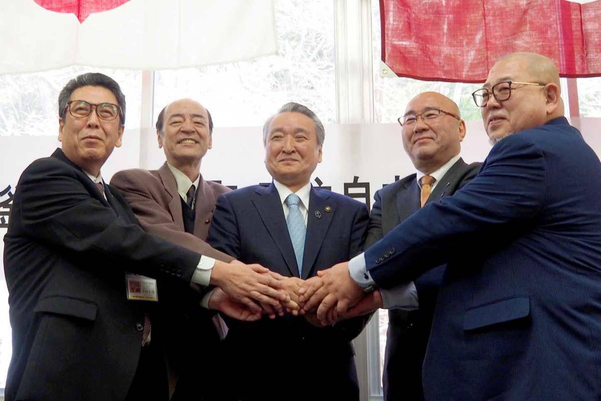 定住自立圏形成の協定締結を終え、握手を交わす釜石市と大槌町の関係者ら